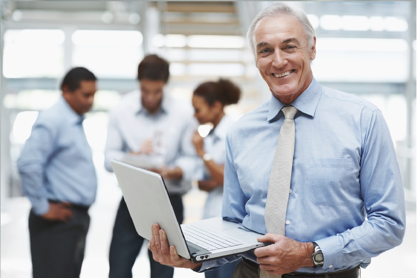 Senior businessman using a laptop with colleagues at the back